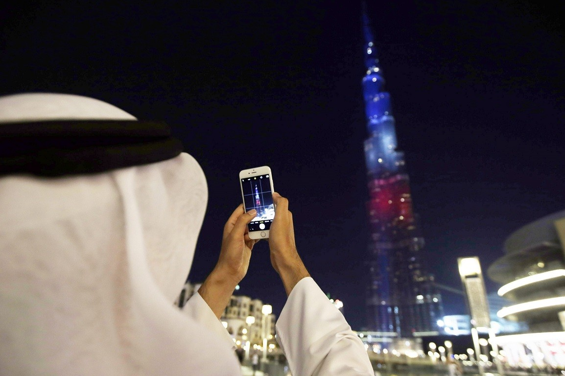 epaselect epa05027298 A man takes a picture of the World's tallest skyscraper Burj Khalifa, which is illuminated in the colours of the French flag in order to show solidarity after the Paris terror attacks of 13 November, in the Gulf emirate of Dubai, United Arab Emirates, 15 November 2015. At least 132 people were killed and some 350 injured in the terror attacks which targeted the Bataclan concert hall, the Stade de France national sports stadium, and several restaurants and bars in the French capital. Authorities believe that three coordinated teams of terrorists armed with rifles and explosive vests carried out the attacks, which the Islamic State (IS) extremist group has claimed responsibility for. EPA/ALI HAIDER